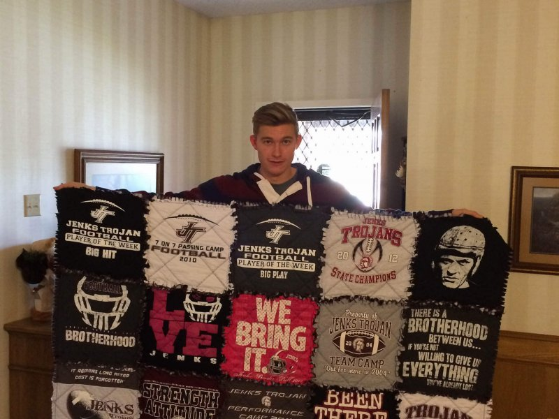 Young man holding a tshirt quilt in maroon and gray colors