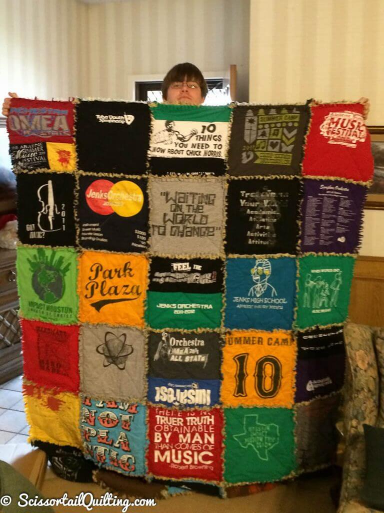 Young man holding a t-shirt quilt