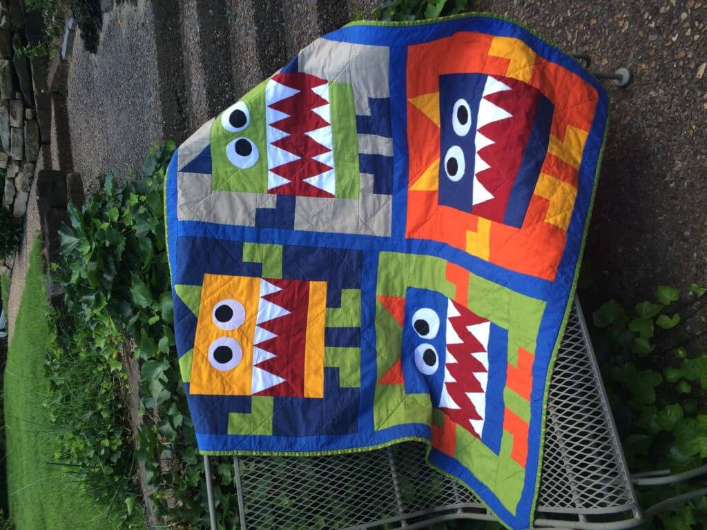 colorful quilt with monsters pieced in design