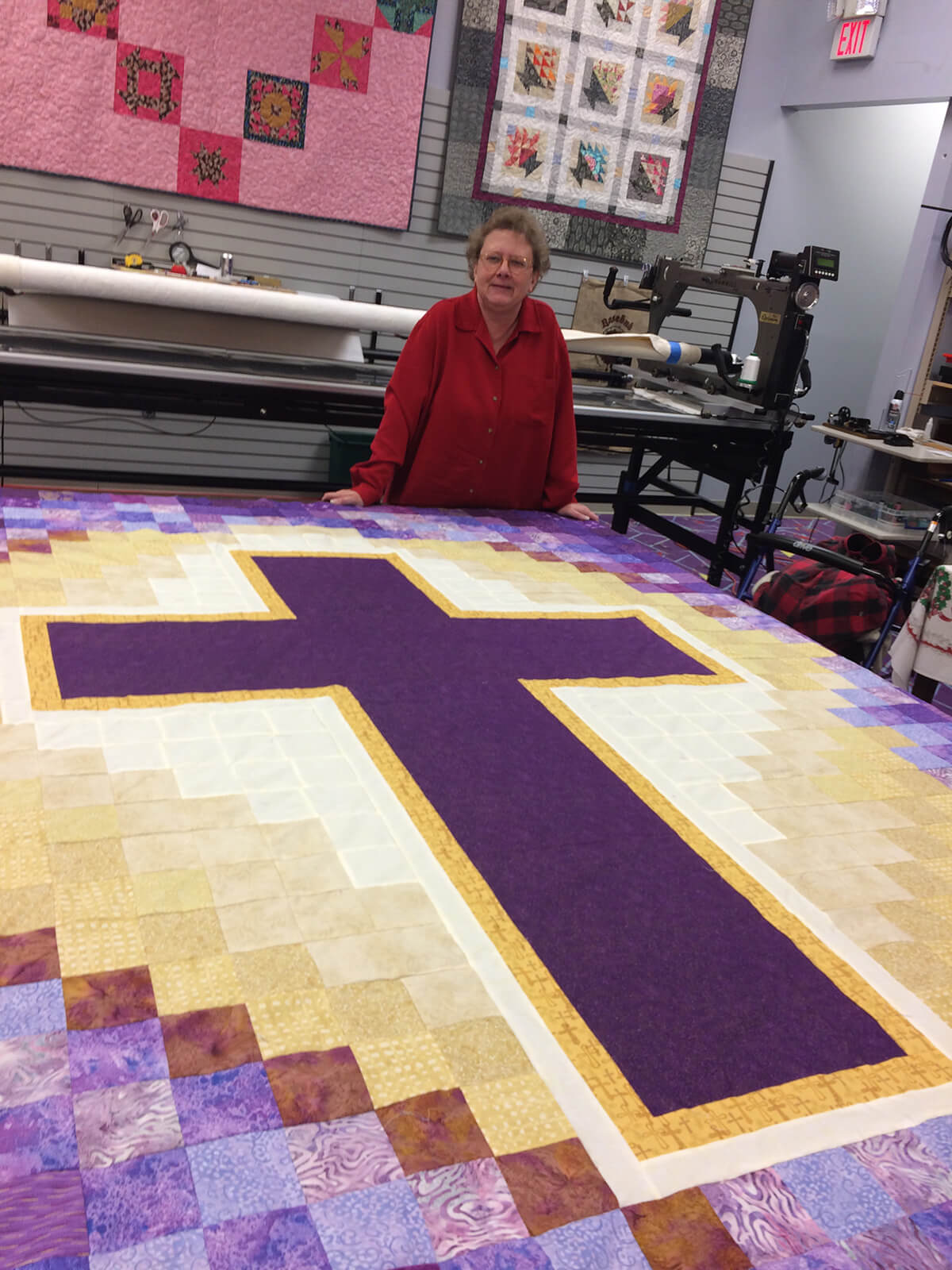 Photo of woman standing behind a quilt top with a cross motif.
