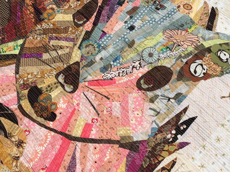 Picture of an art quilt depicting a squirrel holding a nut