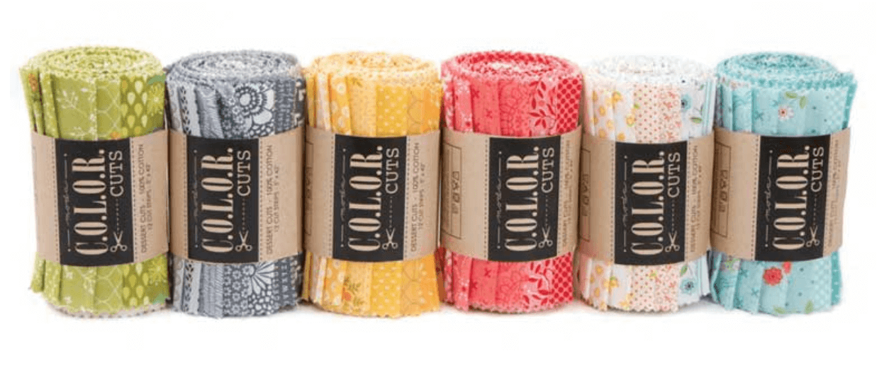 Photo of precut bundles of fabric by Moda sorted by color