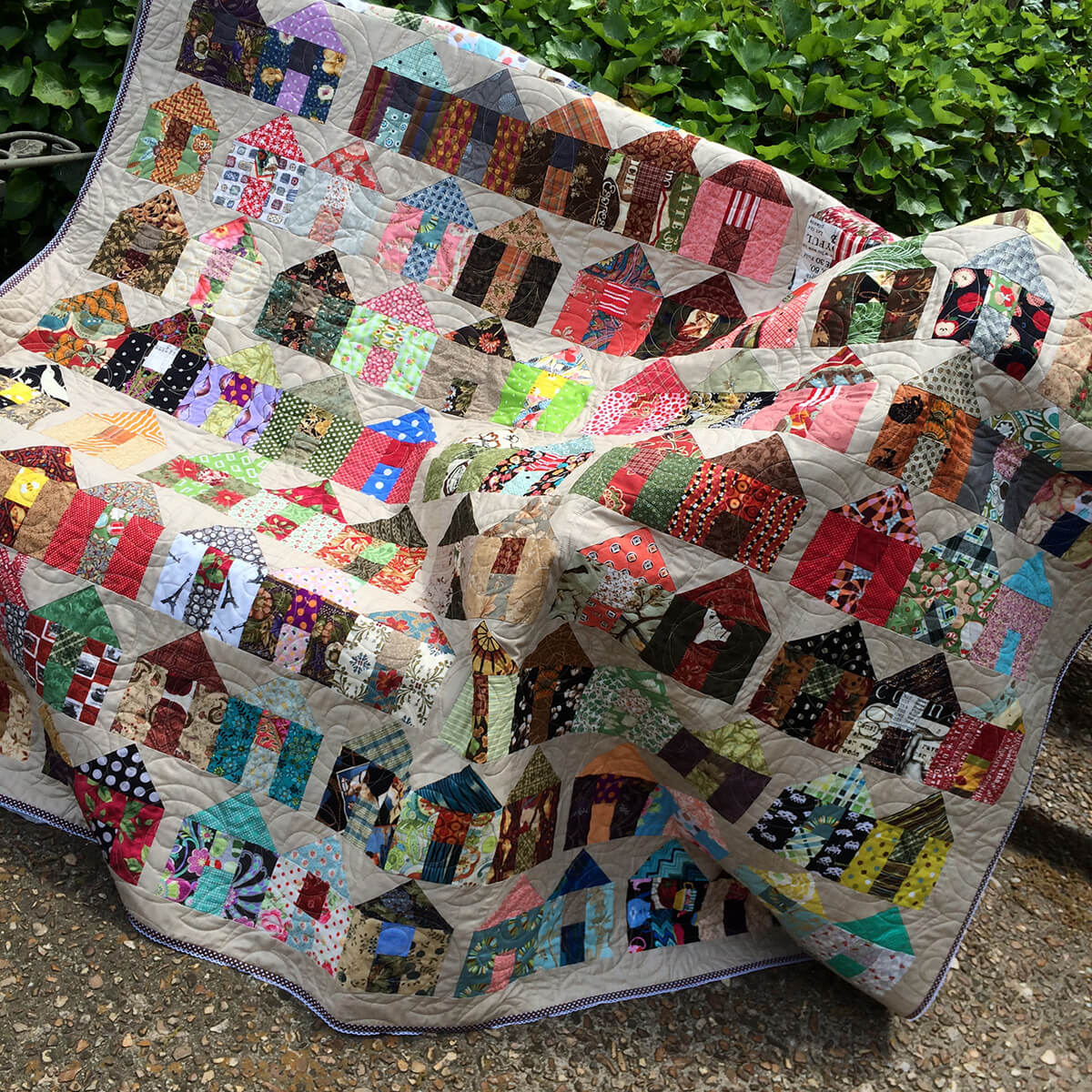 Photo of a scrappy quilt made with house quilt blocks