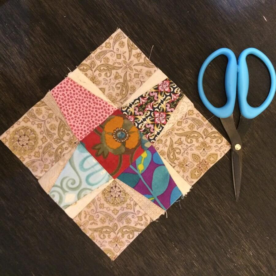 Photo of a Tumble Jack Quilt Block beside a pair of scissors