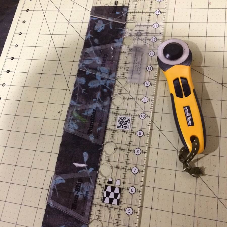 Creative Grids Tumbler Ruler with a strip of fabric
