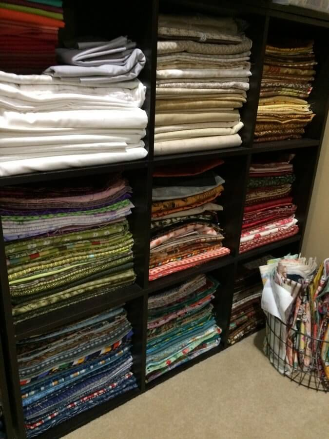 Photo showing shelves of fabric in nearly organized stacks