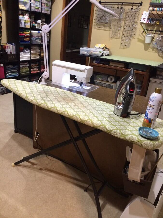 Photo of a room set up with sewing station and ironing board