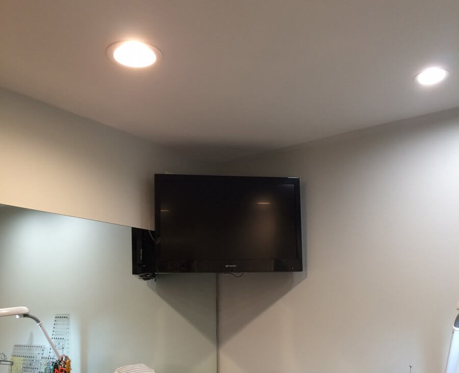 Photo of TV mounted in corner of sewing room
