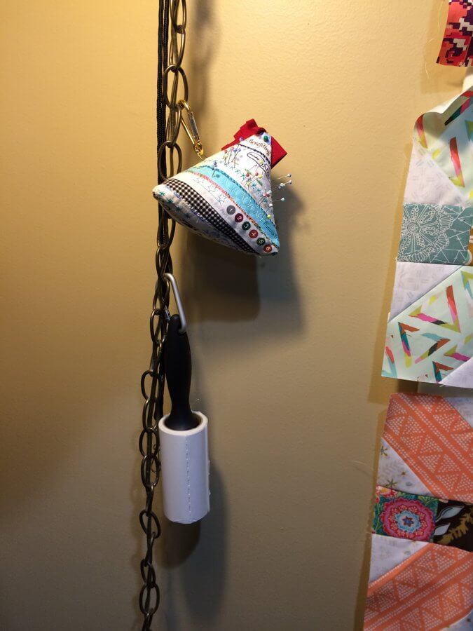 Photo of a chain from a hanging lamp with a pin cushion and lint roller hanging from it
