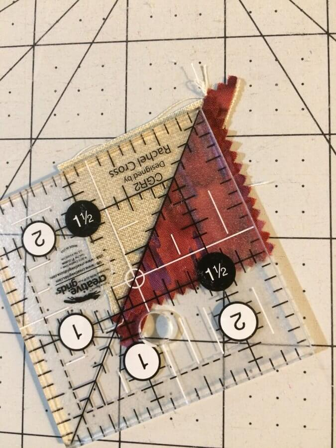 Photo of a clear acrylic ruler used to trim a Half Square Triangle made from a leftover Quick Corner