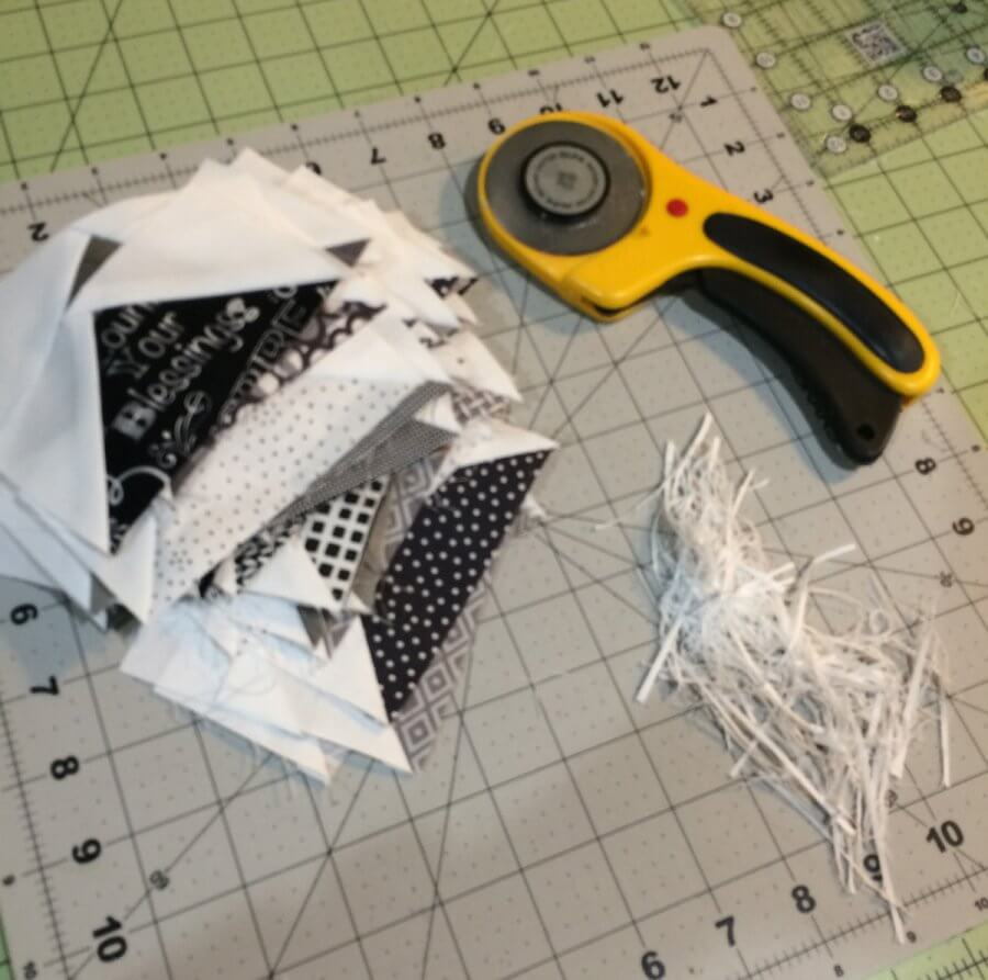 Photo of a stack of trimmed flying geese quilt block units beside a yellow Olfa rotary cutter