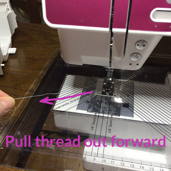 photo showing proper way to pull thread out of a sewing machine