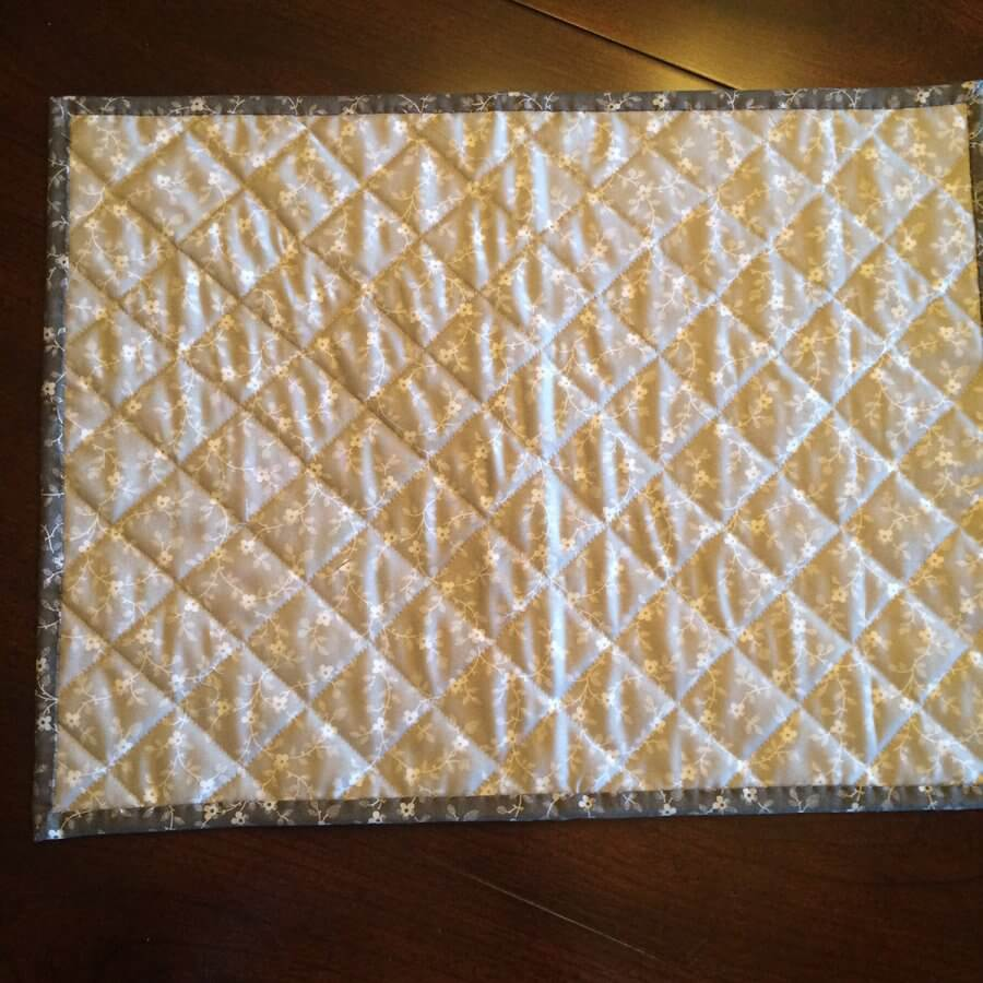 Photo of back side of tiny geese placemat, showing grid quilting lines