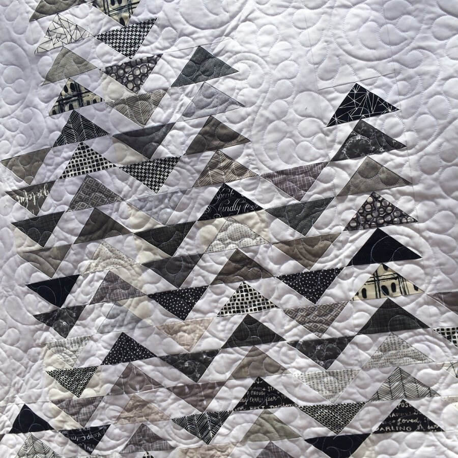 Closeup photo of Sky Quilt Pattern with white background and gray flying geese