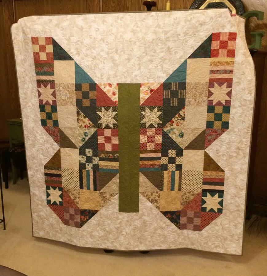 Picture of a quilt with blocks in shape of a butterfly
