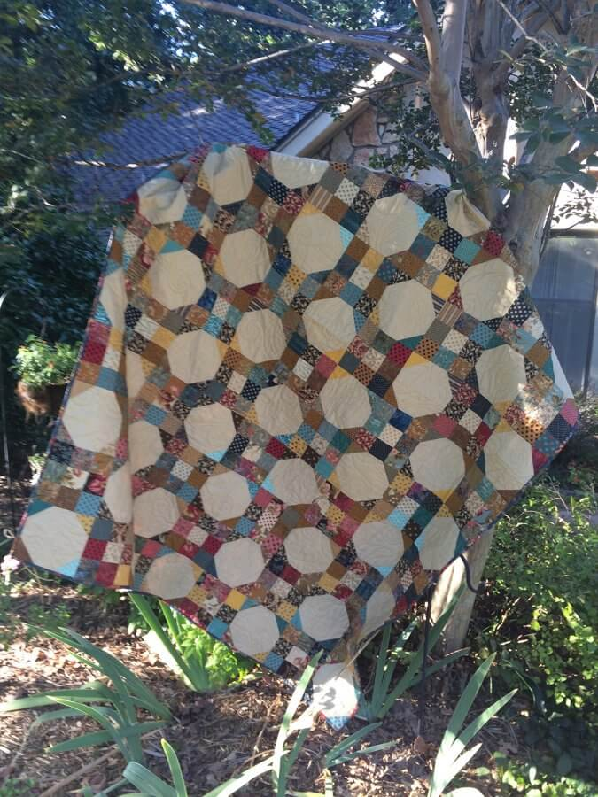 photo of 9-patch snowball quilt hanging on ladder under a tree