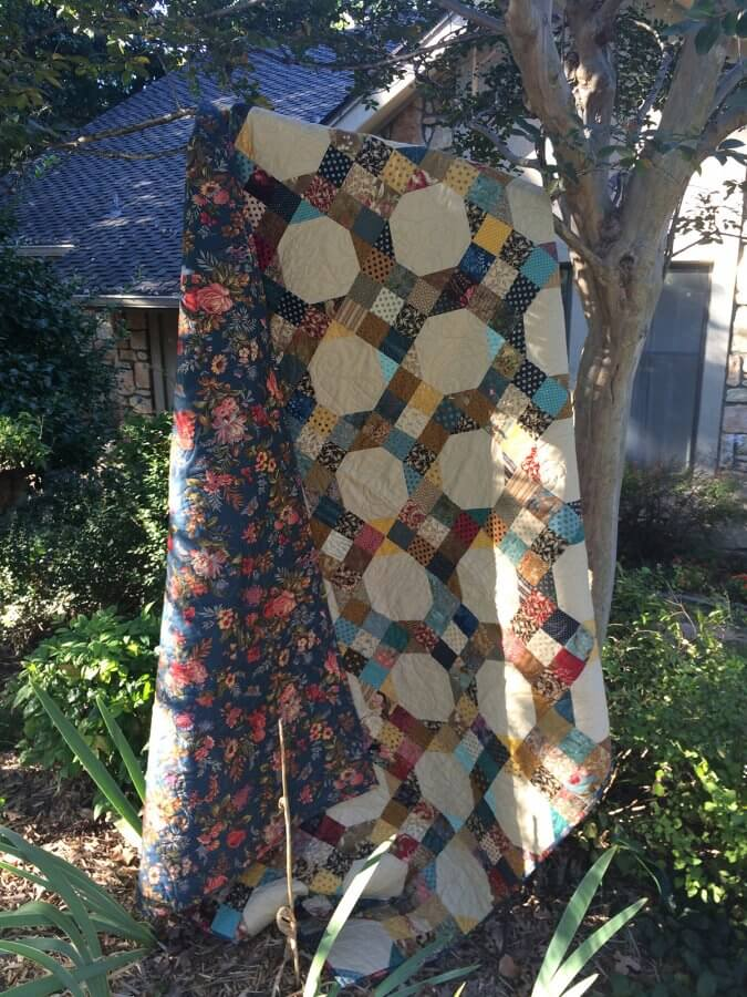 photo of 9-patch snowball quilt under tree swaying in wind